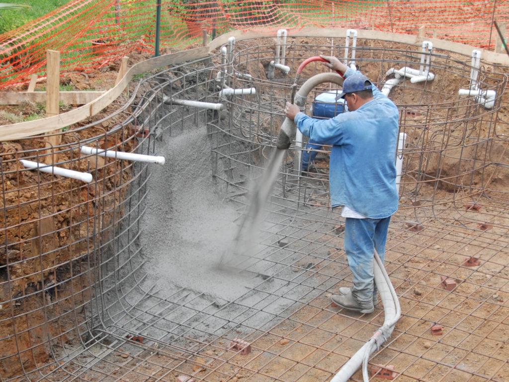 Homme remplie une piscine creusée en béton
