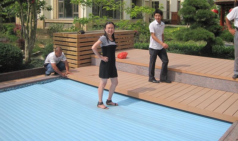 personne assise sur volet couverture de piscine